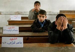 Palestinian schoolboys sitting beside the empty seats of friends who were killed in Israel's Decemeber 08/January09 bombing raid on Gaza.