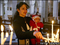Woman lights a candle at St Catherine's Church, Bethlehem